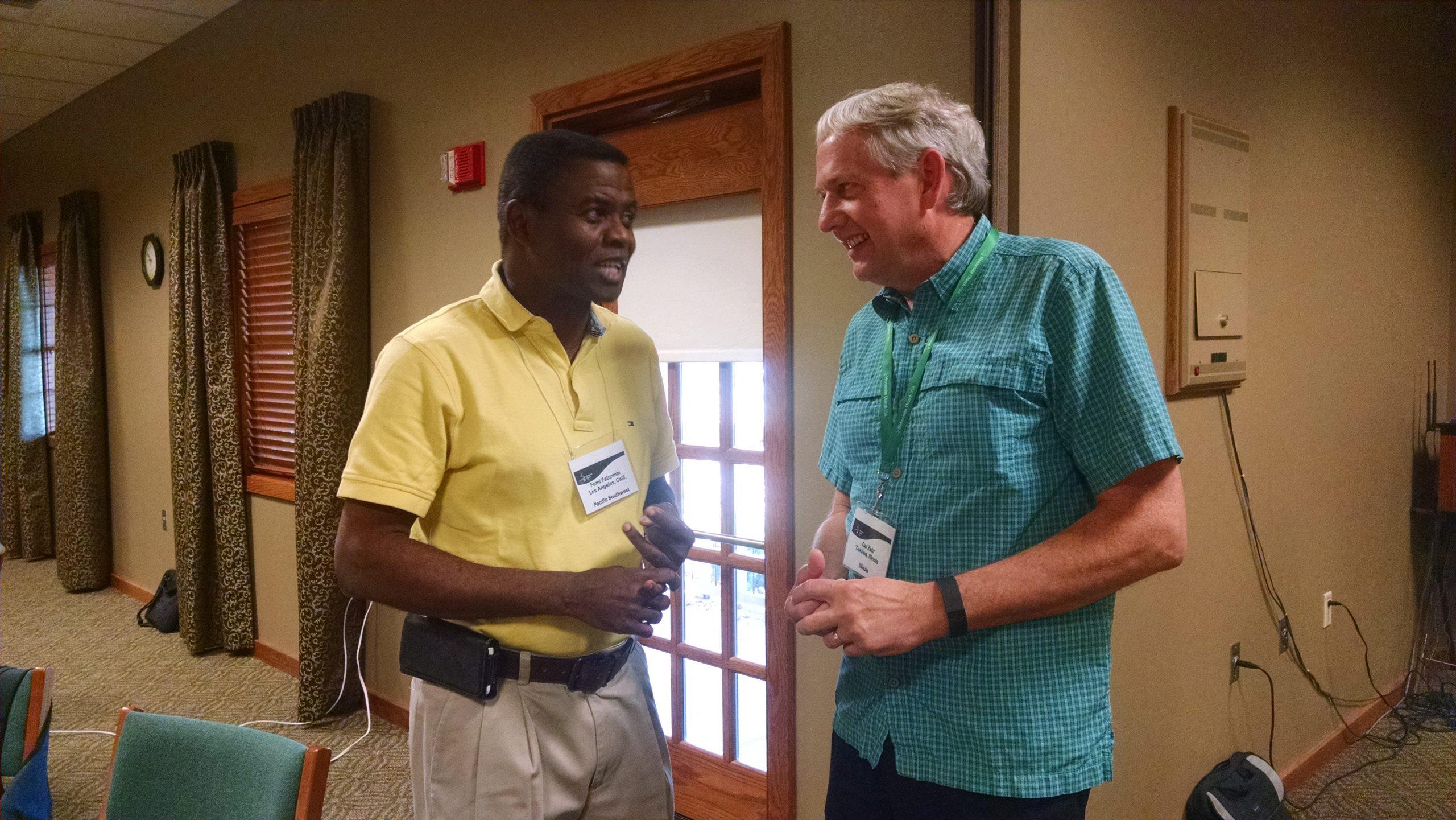 Femi Fatunmbi, moderador de la Conferencia Menonita Pacific Southwest, y Cal Zehr, moderador de la Conferencia Menonita Illinois, de visita durante un receso en la reunión del Concilio de Líderes Constituyentes llevada a cabo en Archbold, Ohio del 19 al 21 de octubre. (Foto de Hannah Heinzekehr.)