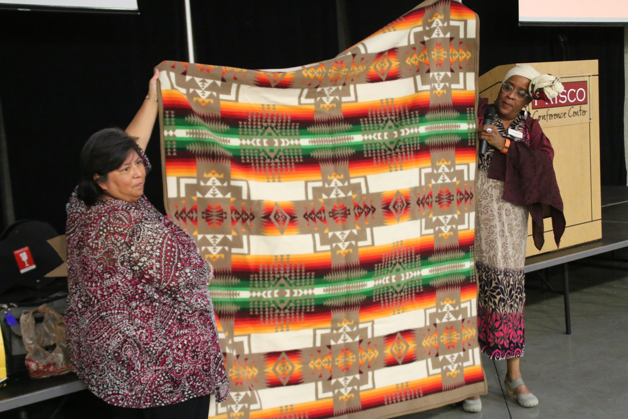 Carol Roth and Michelle Armster presenting Lawrence a Pendleton Blanket (Betty received a Cheyenne inspired quilt).