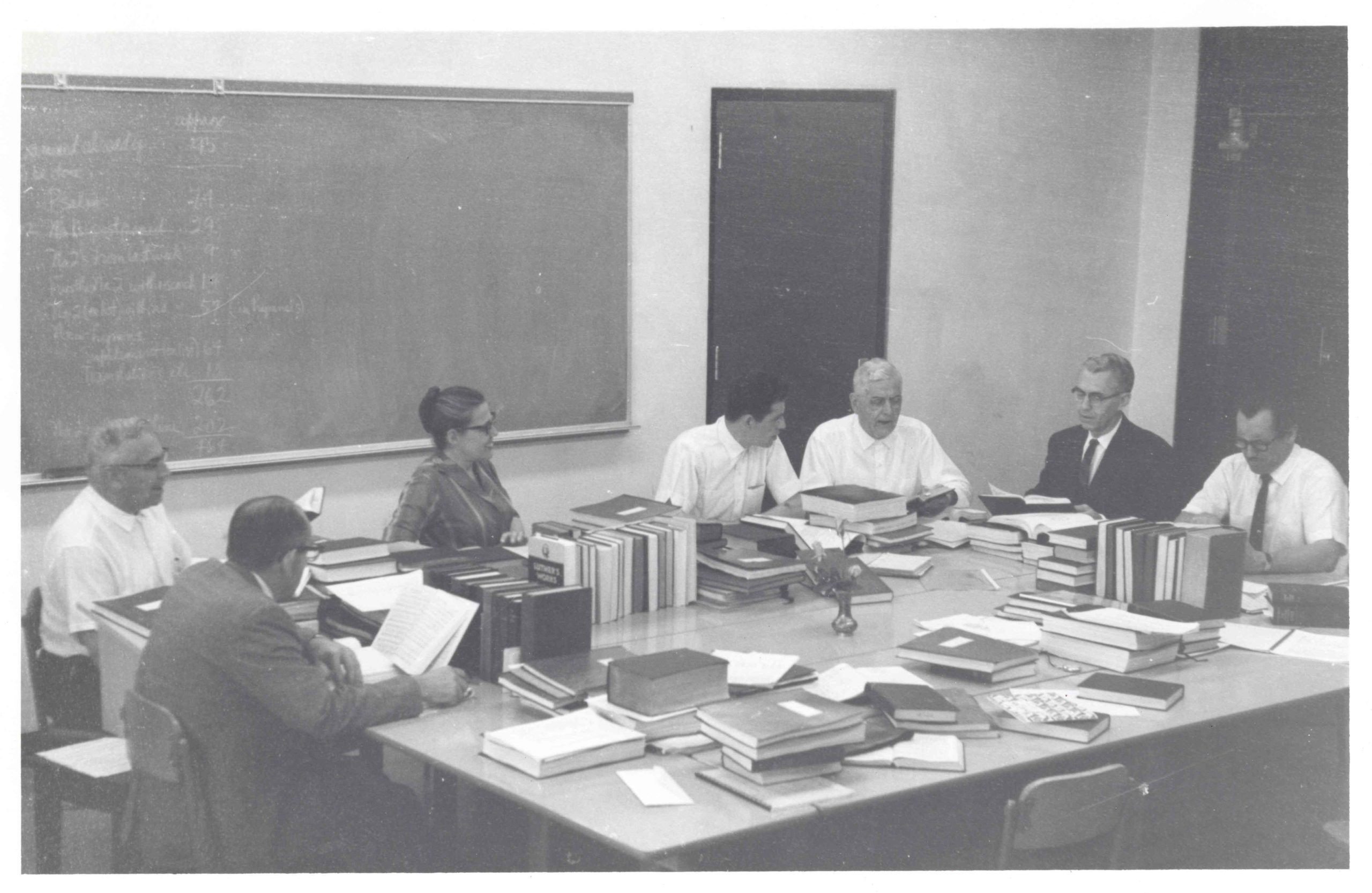A meeting of the Joint Worship and Hymnal Committee. This committee produced the 1969 Mennonite Hymnal, with Mary Oyer acting as Executive Secretary. Starting from bottom left, and moving clockwise around table: Ed Stoltzfus, Paul Erb, Mary Oyer, John Ruth, Chester Lehman, Marvin Dirks, and Walter Klaassen.