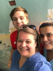 Photo of Amy Yoder McGloughlin and son, Will, visiting with CPT Palestine Team Leader Mona Al Zuhairi (right) in 2018.