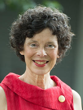 A middle-aged woman with short, curly brown hair, wearing a red blouse.